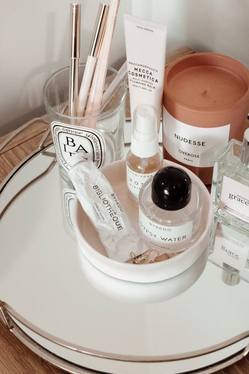 Various cosmetic products with perfumes and makeup brushes in glass and scented candle placed on metal tray