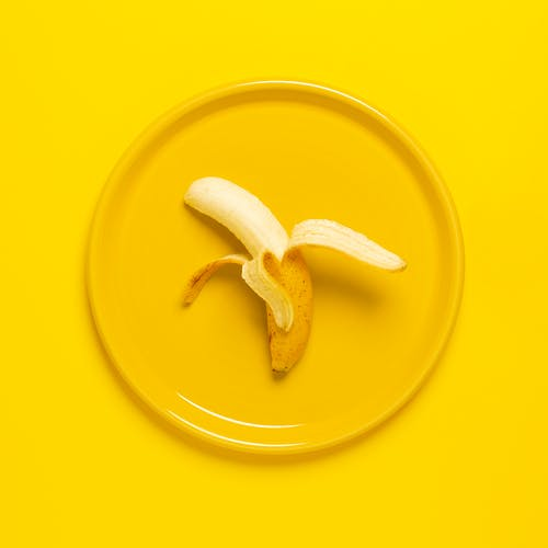 Photo of Peeled Banana on Yellow Plate and Background