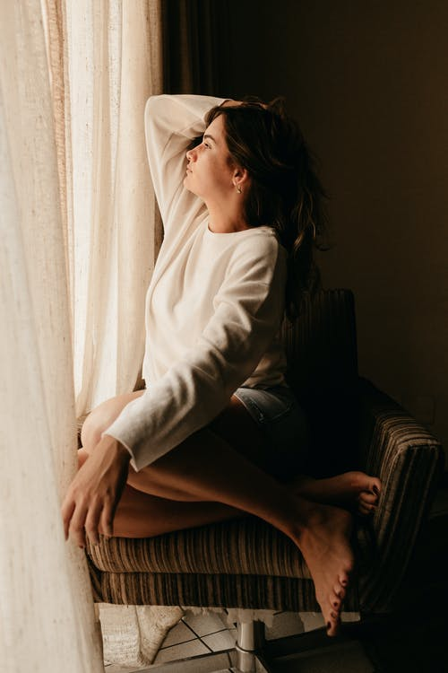 Photo of Woman Sitting on Armchair Beside Window Looking Outside