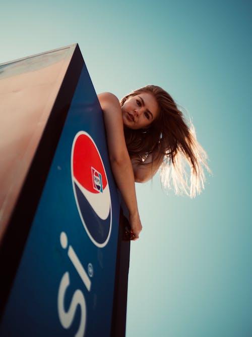 Low Angle Photo of Woman on Top of Pepsi Fridge Posing