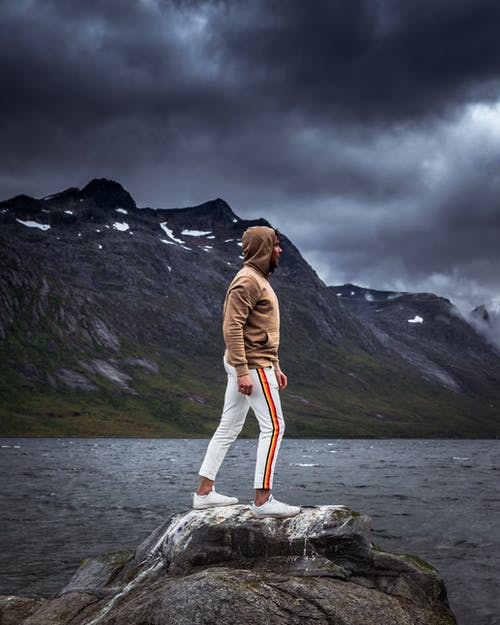 Person Wearing White and Orange Sweat Pants and Brown Sweatshirt Standing on Rock Near Body of Water