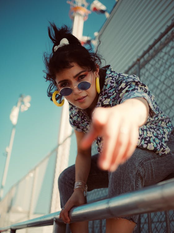 Selective Focus Photo of Woman in Floral Shirt, Grey Jeans, and Sunglasses Pointing Finger