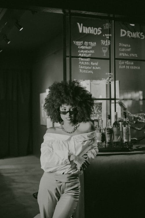 Grayscale Photo of Posing Woman in Off-shoulder Dress Leaning on Bar Counter Looking Away