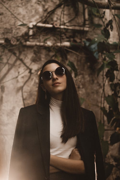 Portrait Photo of Woman in Black Sunglasses and Black Coat Posing With Her Arms Crossed