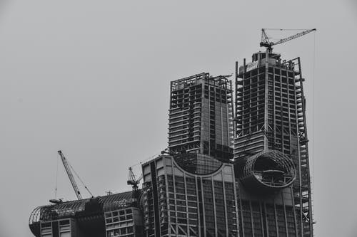 Grayscale Photography of High-rise Building With Tower Cranes