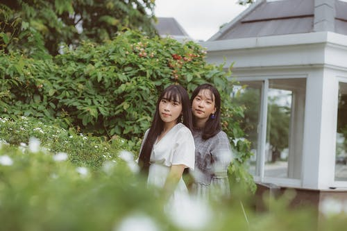 Photo Of Women Standing Near Plants