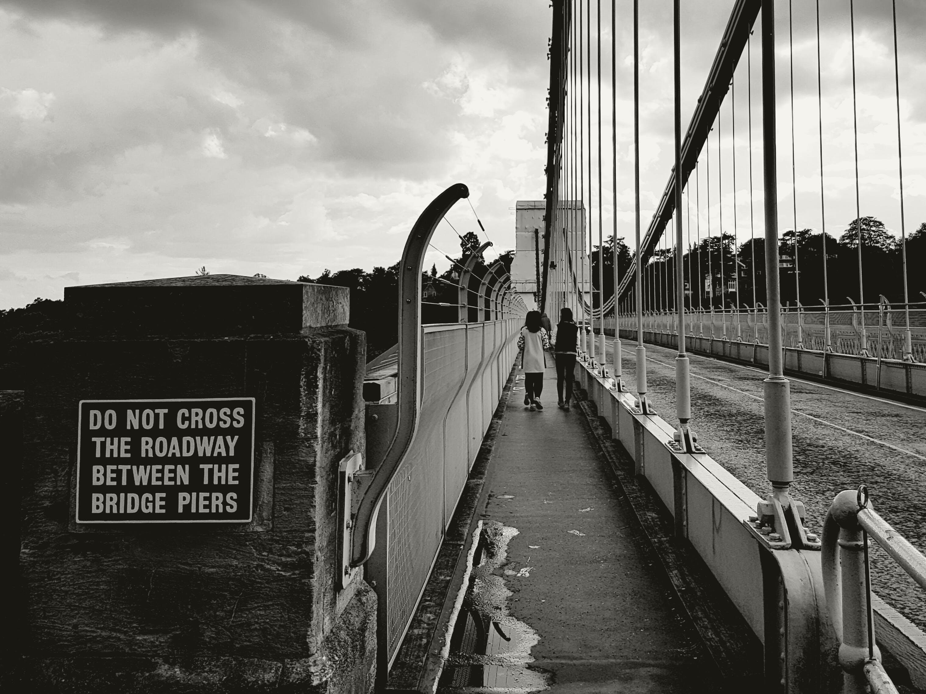 Two People Walking on the Sidewalk of the Bridge