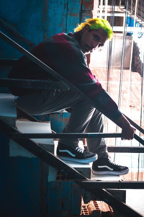 Photo of Man in Luminous Green Hair Sitting on Stairs Posing