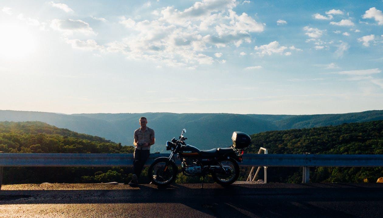 Man Leaning on Metal Frame Beside Motorcycle