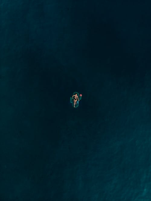Aerial Photo of Woman Lying on Inflatable Floater in the Middle of Ocean