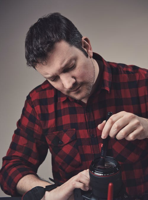 Man Wearing Red Plaid Shirt Holding Digital Camera