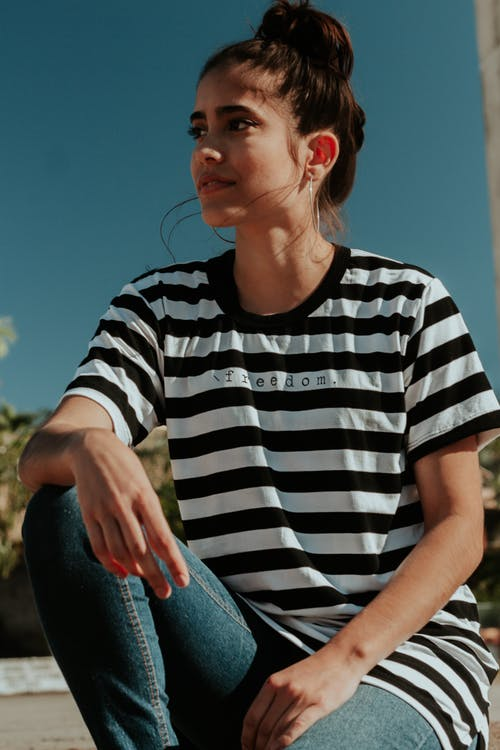 Photo of a Woman Wearing  White and Black Striped Crew-neck T-Shirt