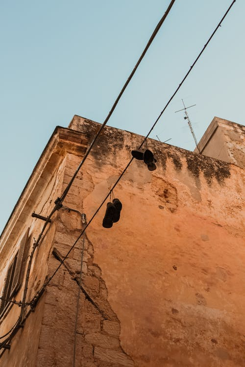 Two Pairs of Shoes Hanging on Electric Cable