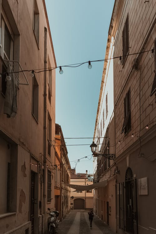 Photo of a Person in the Middle of Narrow Alley In Between Buildings
