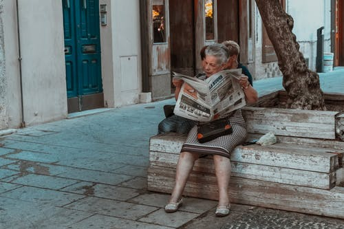 Woman Sitting on a Wooden Bench Reading a Newspaper