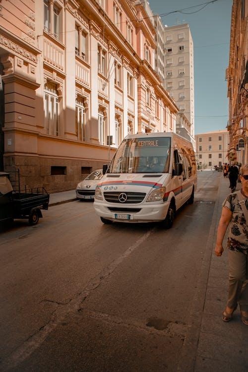 Mercedes-benz Van on Road in Between Two Buildings