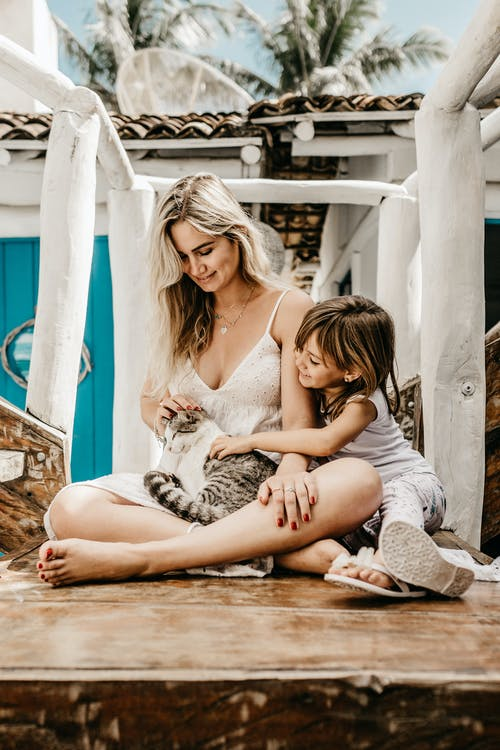 Woman and her Child Sitting while Holding a Cat