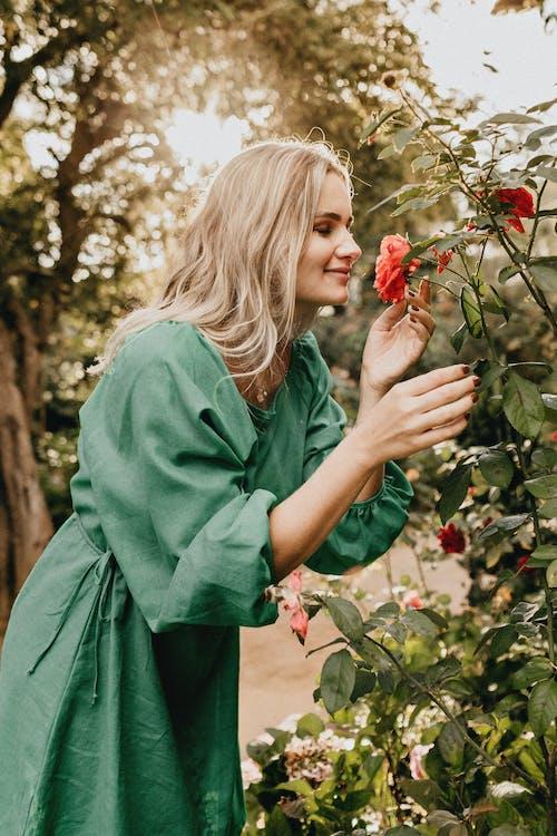 Woman Wearing a Green Long-sleeved Dress Smelling a Flower