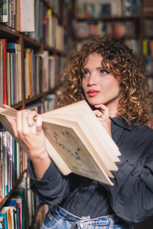 Photo of a Woman Holding a Book In Library