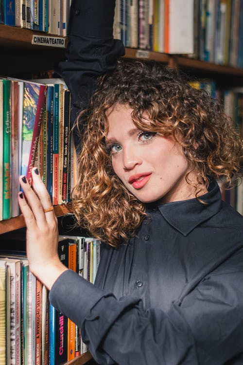 Photo Of Woman Beside Bookshelf