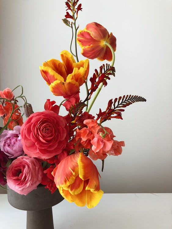Bunch of fresh flowers including roses tulips and peonies In gray vase on white table