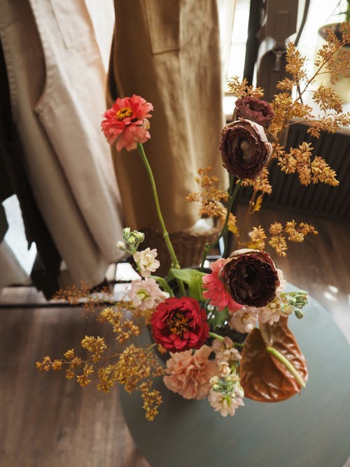 Top view of colorful bouquet of long flowers in vase on coffee table next to clothes on hanger