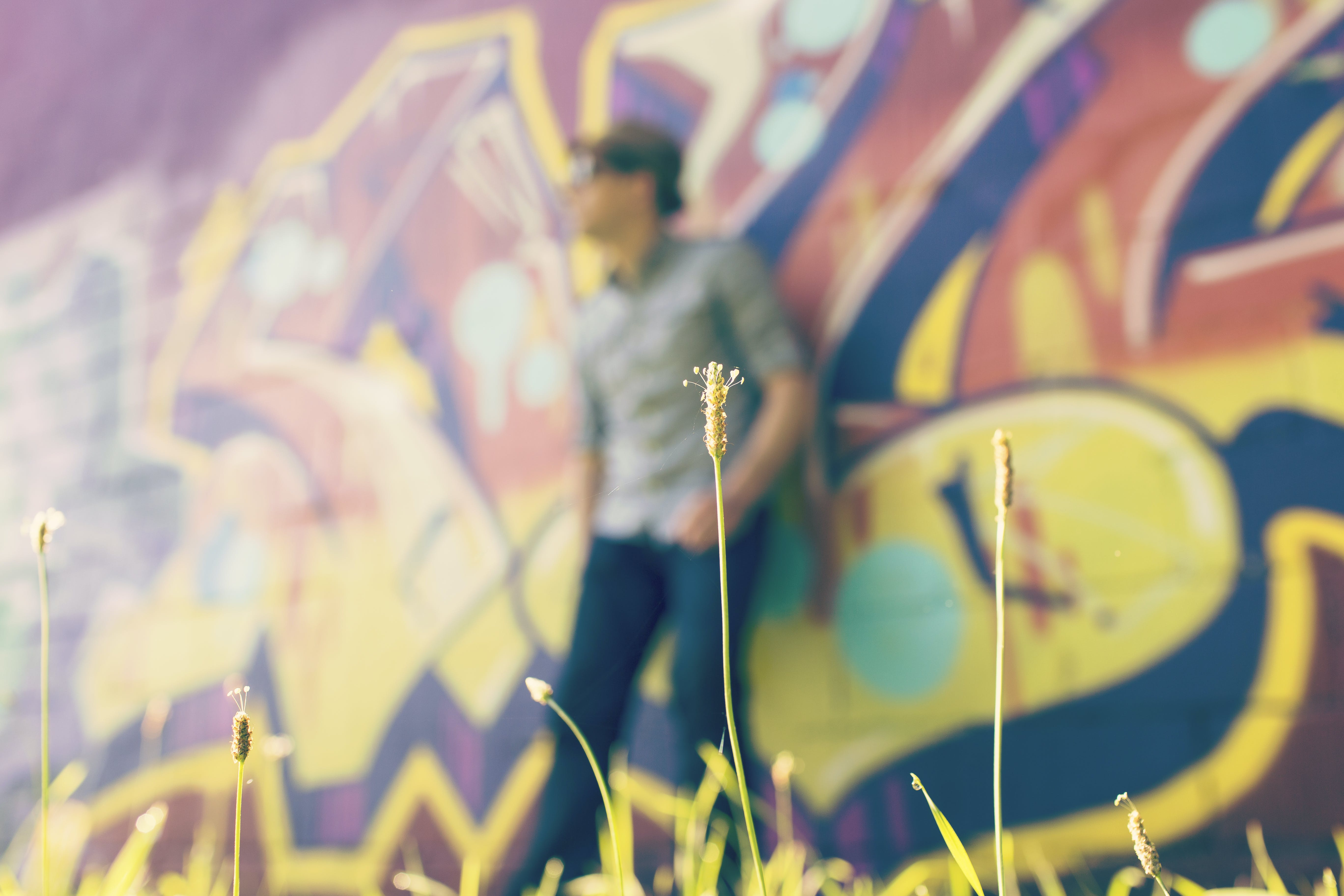Shallow Focus Photography of Person Leaning on Wall