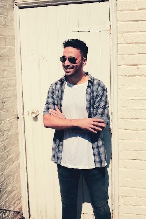 mies hymyilee, seinän vieressä