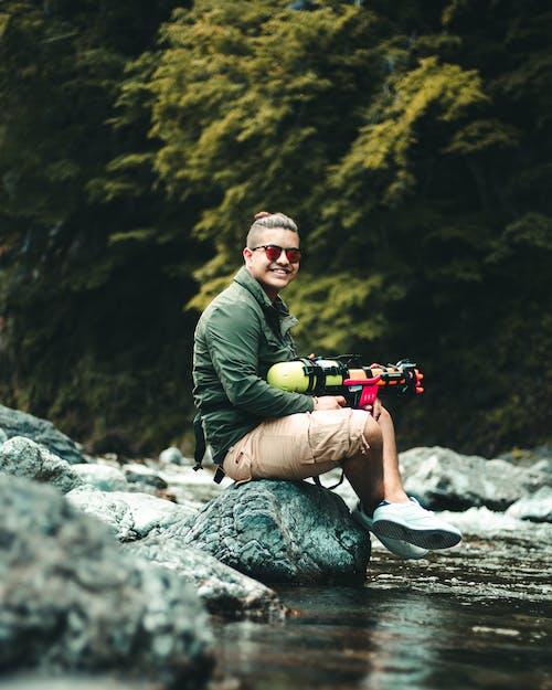 Mann Mit Einer Spielzeugpistole, Die Auf Einem Felsen Boulder Sitzt