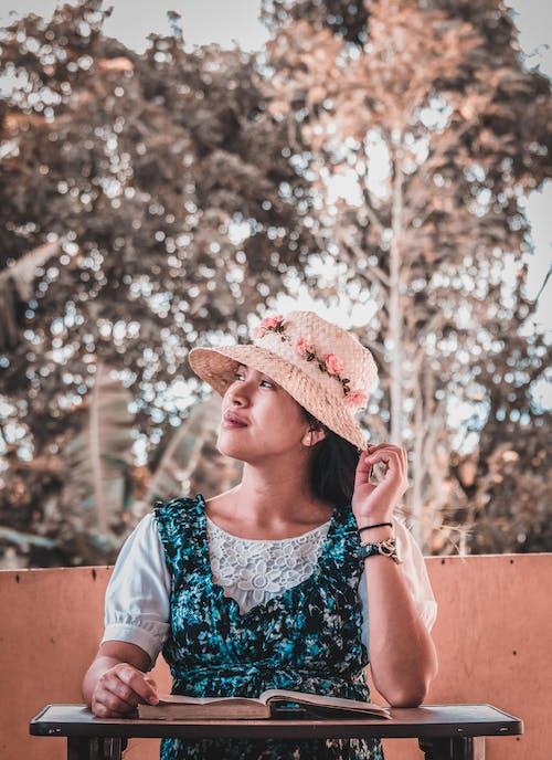 꽃무늬 드레스, 다른 곳을 바라보는, 밀짚모자, 앉아 있는의 무료 스톡 사진