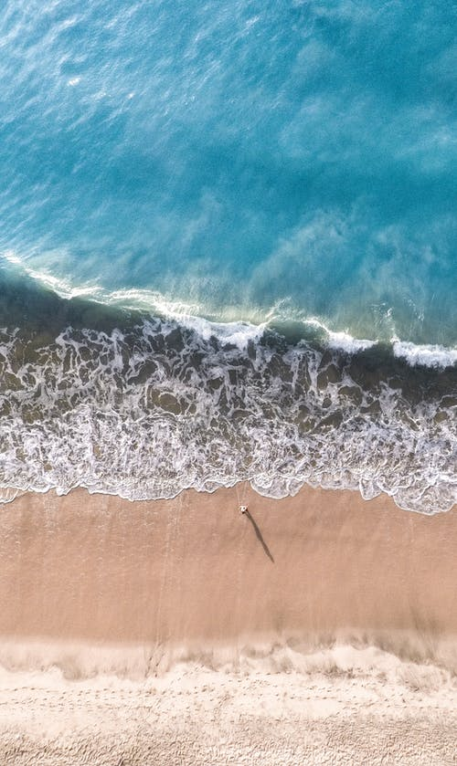 Aerial Photography of Person Standing on Seashore
