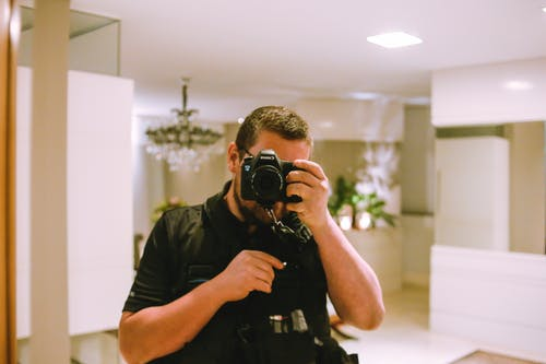 Man Using Black Dslr Camera