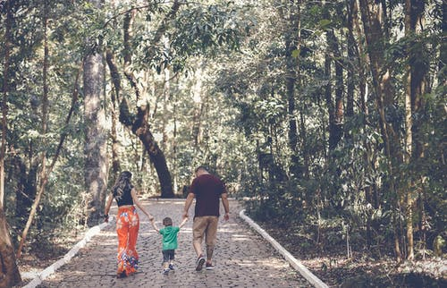 Man, Woman, and Child Walking on Walkway