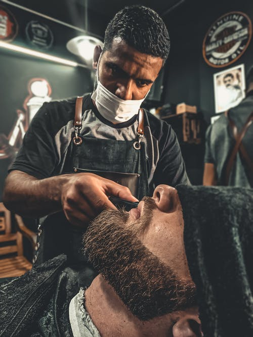 A Barber Grooming A Man's Beard