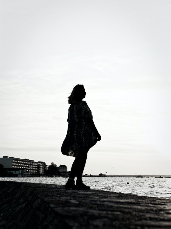 Silhouette of Woman Standing Beside A Body Of Water