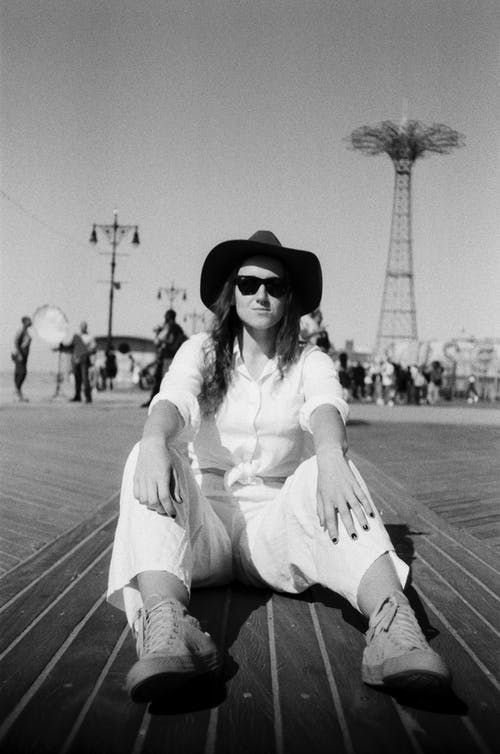 Gray scale Photo of Woman Wearing White Top and White Pants
