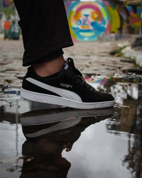 A Person in White and Black Puma Suede Shoe