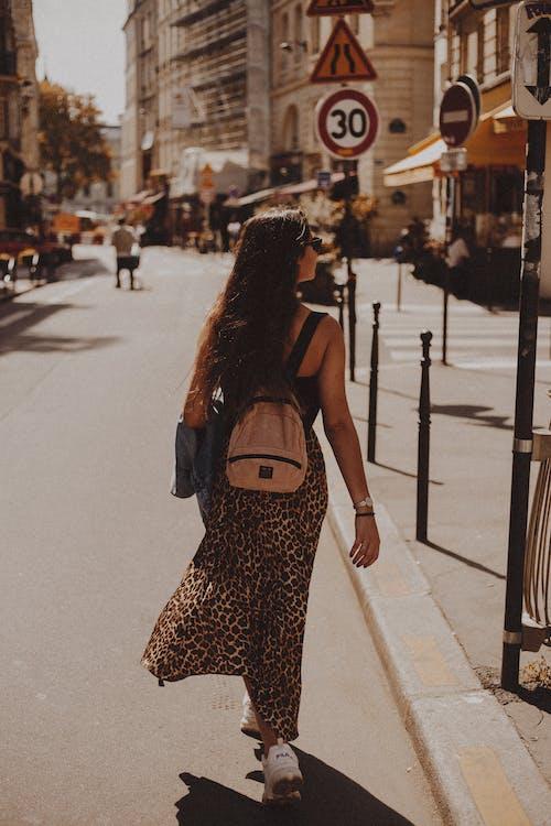 Вид сзади женщины с рюкзаком, идущей по улице
