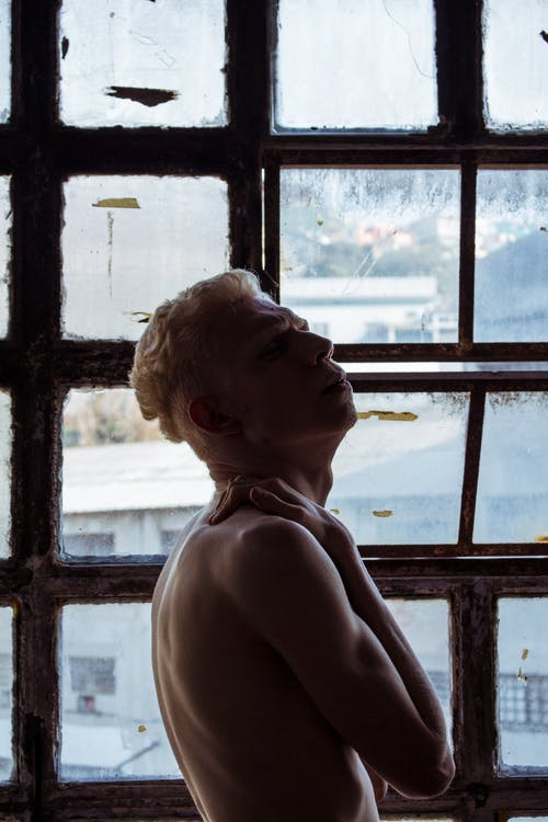Photo Of Man Standing Near Window