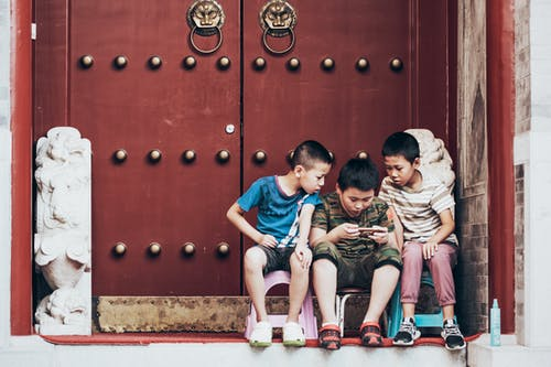 Three Boys Sitting Beside Door