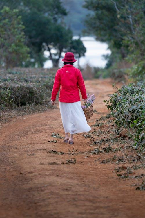 一個女人走在提著籃子的道路上
