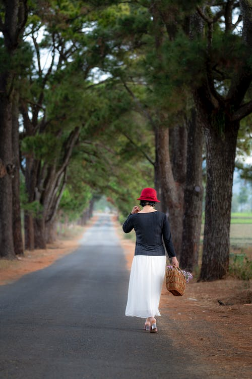 Woman Standing on Concrete Road at Middle of Trees