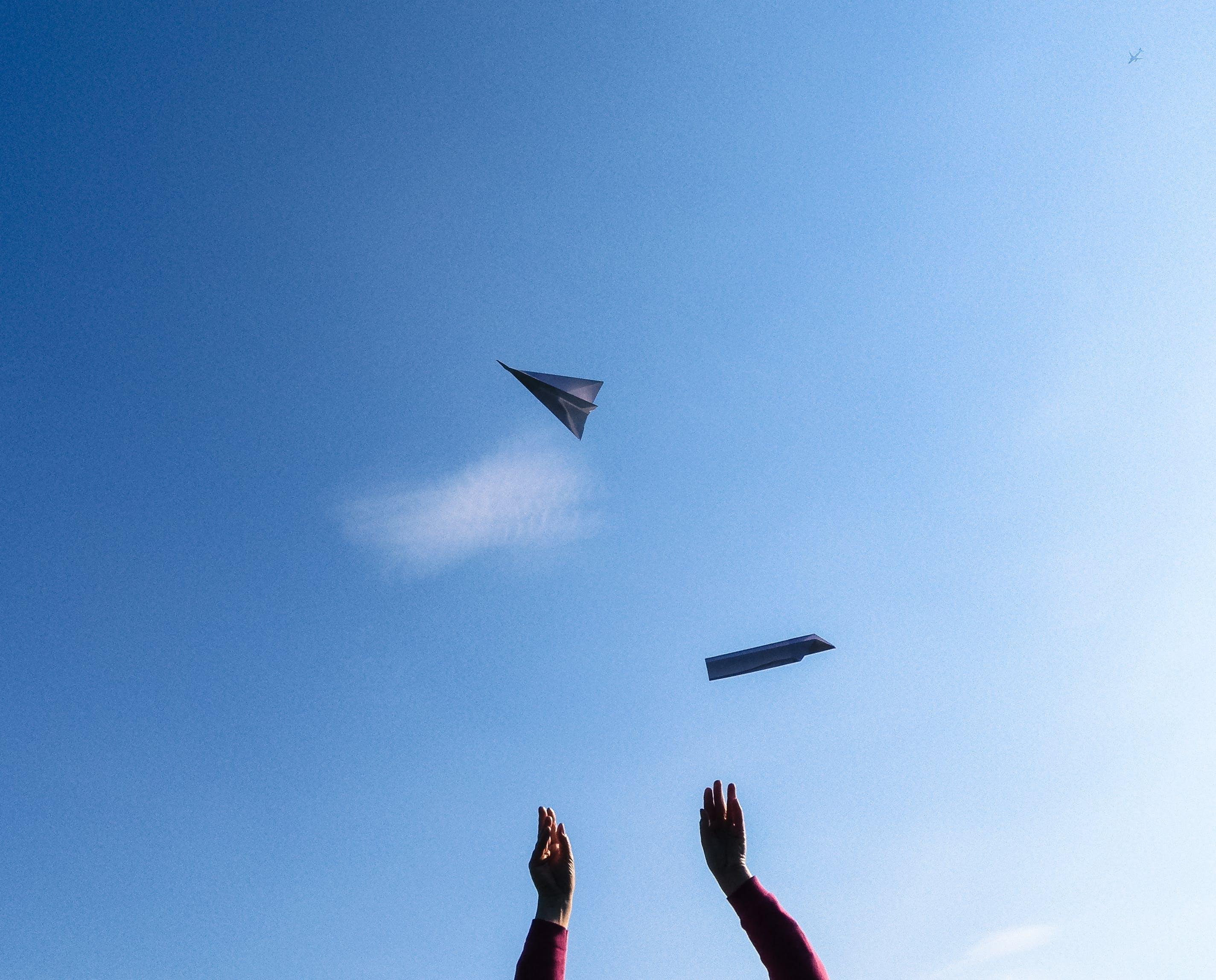 Free stock photo of blue, flight, hands, paper aeroplane