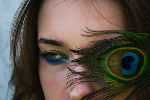 A Feather Covering An Eye Of A Woman's Face