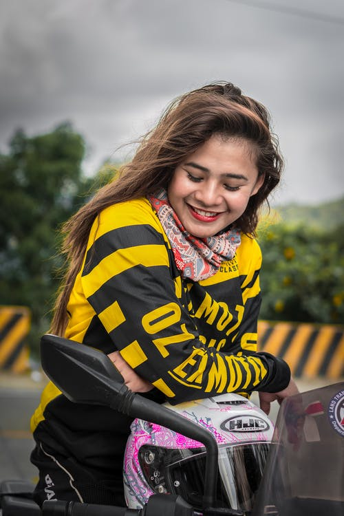A Smiling Woman Riding A Motorcycle