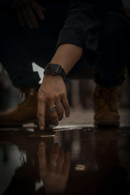 Adam Yerdeki Su Kalıntısına Dokunmak Için Oturuyor
