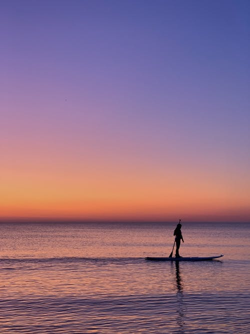 Silhouette of Person Riding Board during Sunset