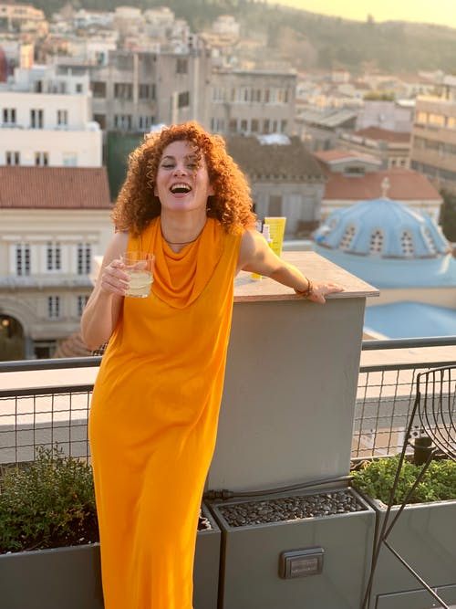 Woman In An Orange Dress Poses In The Balcony