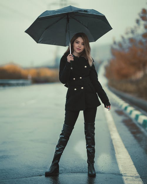 Woman Standing On A  Road Holding An Umbrella
