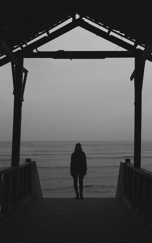 A Woman Standing On A Boardwalk
